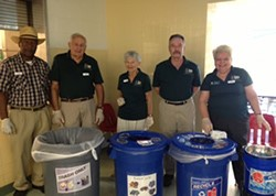 James City County Clean County Commission volunteers stand in front of recycling containers.